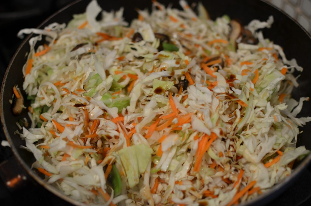 Cole slaw mix added to the wok with soy sauce and celery seed.